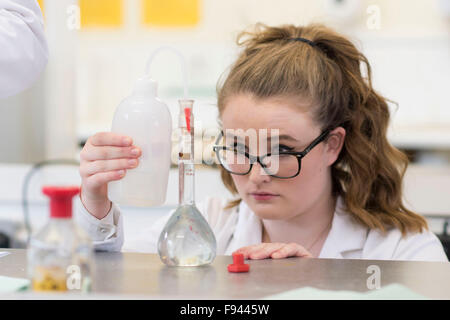A sixth form Chemistry student performs a practical experiment during a A Levels science class. - Stock Photo