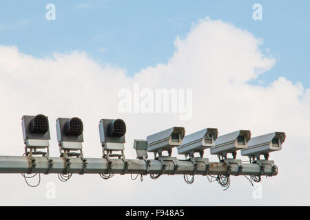Four security cameras and cloudy sky mounted on traffic pole - Stock Photo