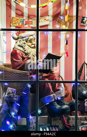 Christmas Santa display in a shop window at Bourton on the Water, Cotswolds, Gloucestershire, England - Stock Photo