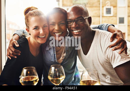 Three ethnic best friends smiling at camera and hugging - Stock Photo