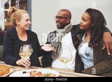 Good friends enjoying dinner outside on a cafe, ethnic friends - Stock Photo