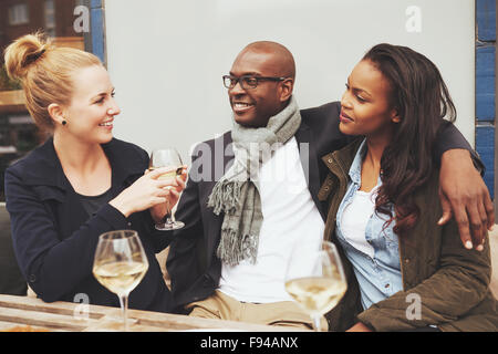 Friends having a conversation at a cafe multi racial friendship - Stock Photo
