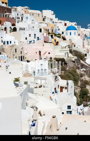 Santorini, Oia. View along town filled with whitewashed, cubiform houses built on steep cliff face, and Greek church - Stock Photo