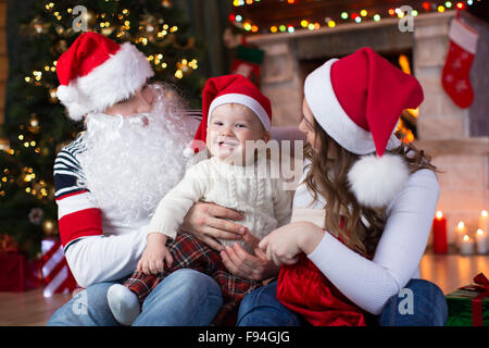 Happy family with child son having a fun near Christmas tree and fireplace  in living room - Stock Photo