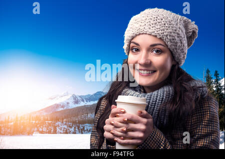 Beautiful young woman with coffe cup enjoying a walk in mountains - Stock Photo