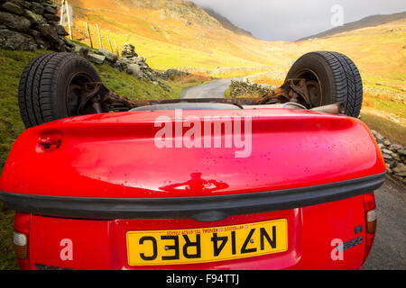 A car overturned on Kirkstone Pass above Ambleside in the Lake District, a victim of Storm Desmond, Cumbria, UK. - Stock Photo