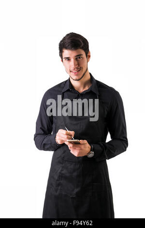 Full length shot of young chef or waiter posing, wearing black apron and shirt, writing order electronic device, - Stock Photo