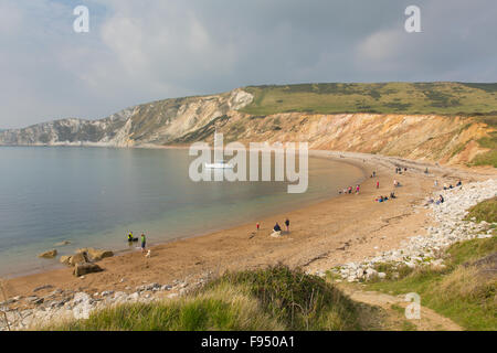 Worbarrow Bay beach with people east of Lulworth Cove and near Tyneham on the Dorset coast England uk with a yacht - Stock Photo
