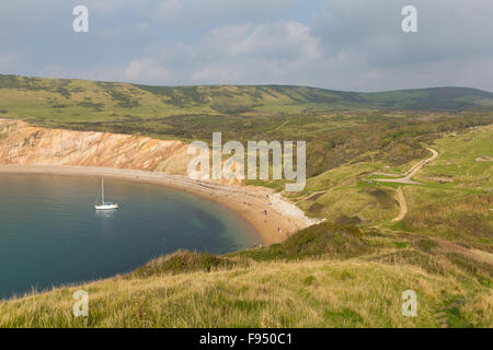 Worbarrow Bay east of Lulworth Cove and near Tyneham on the Dorset coast England uk with a yacht - Stock Photo
