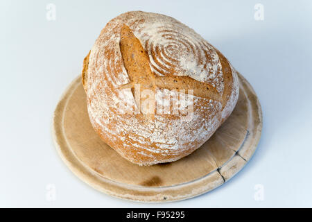 A homemade freshly baked loaf of sourdough bread on a breadboard - Stock Photo