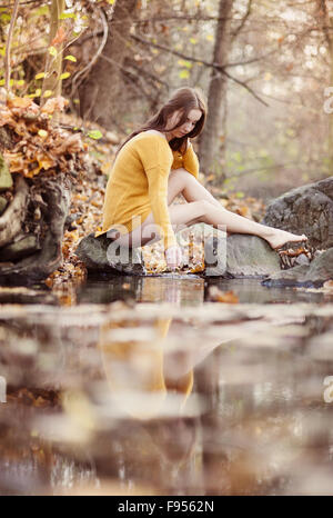 Outdoor portrait of beautiful girl in autumn forest - Stock Photo
