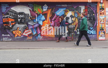 Young man and woman walking past some street art on shutters in Stevenson Square, Lever Street, Manchester city - Stock Photo