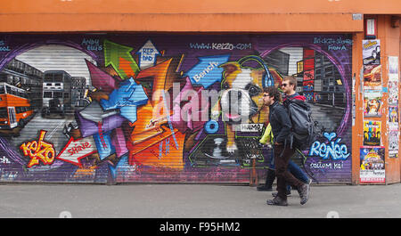 3 young men walking past some street art on shutters in Stevenson Square, Lever Street, Manchester city centre, - Stock Photo
