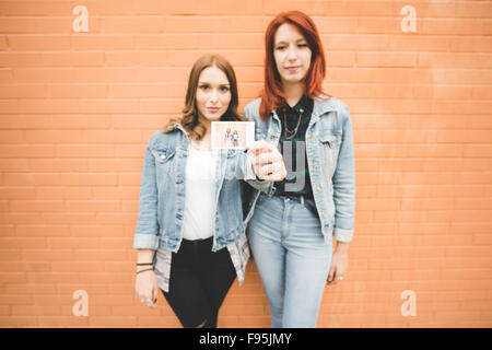 Knee figure of two young handsome caucasian blonde and redhead straight hair women posing leaning against a brick - Stock Photo