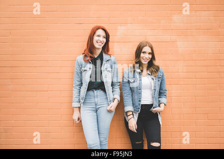 Knee figure of two young handsome caucasian blonde and redhead straight hair women posing leaning against a wall, - Stock Photo