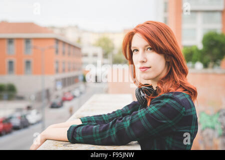 Half length of young handsome caucasian redhead straight hair woman leaning on a handrail, overlooking left, serene, - Stock Photo