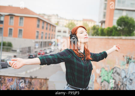 Half length of young handsome caucasian redhead straight hair woman listening music with headphones, feeling free - Stock Photo