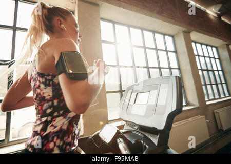 Young focused female working out at gym jogging on a treadmill. Fitness woman doing running exercise in the health - Stock Photo