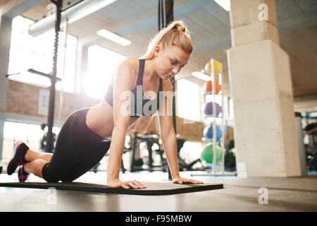 Attractive young female doing push ups on exercise mat. Fitness woman working out in gym. - Stock Photo