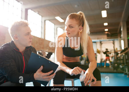 Shot of a personal trainer and young woman discussing fitness plan. Personal trainer showing something on clipboard - Stock Photo