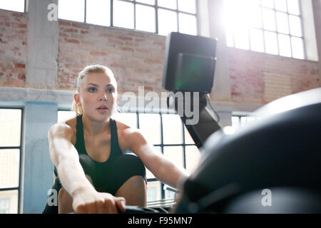 Fit young woman working out on a rowing machine at the gym. Caucasian female doing cardio exercise in fitness club. - Stock Photo