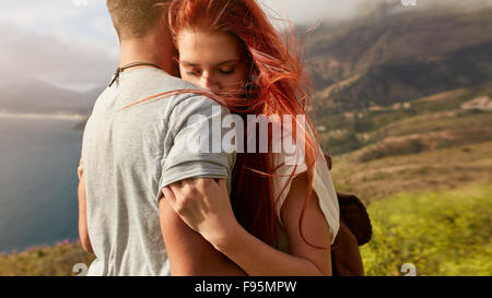 Close up shot of young woman hugging her boyfriend. Young couple in love embracing outdoors. - Stock Photo