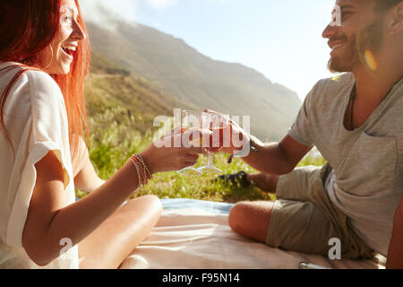 Shot of a cheerful young couple drinking wine and enjoying a picnic.  Young man with her girlfriend on vacation sitting on grass