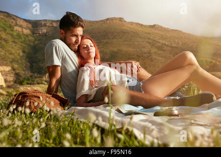 Portrait of loving young couple relaxing on summer picnic. Two young people on a mountain sitting together relaxing. - Stock Photo