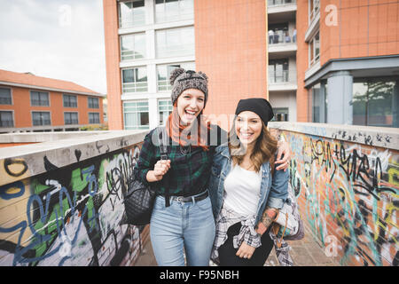 Knee figure of two young handsome caucasian blonde and redhead straight hair women walking hugging outdoor in the - Stock Photo