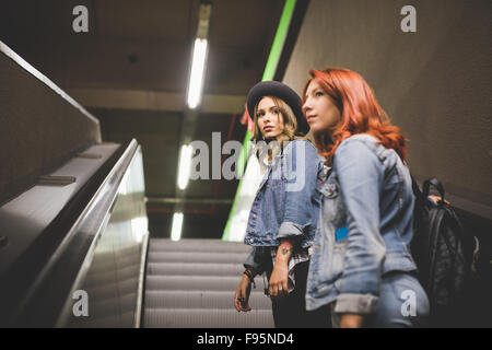 Knee figure of two young handsome caucasian blonde and redhead straight hair women using escalator in the subway, - Stock Photo