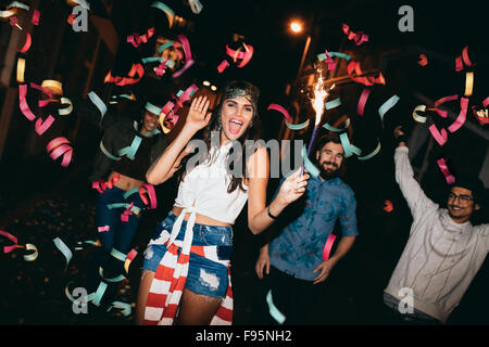 Portrait of crazy young people celebrating outdoors. Young friends partying outdoors with sparklers and confetti - Stock Photo