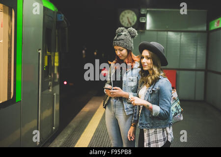 Knee figure of two young handsome caucasian blonde and redhead straight hair women waiting in the underground for - Stock Photo