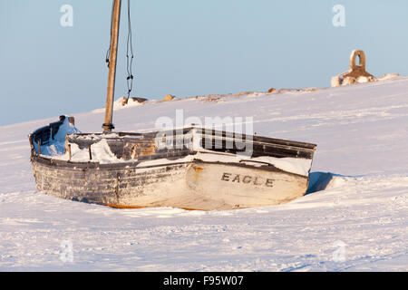 A boat sits on the shores of Cambridge Bay, Nunavut, Canada - Stock Photo
