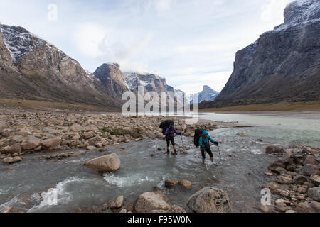Hikers cross a creek in Auyuittuq National Park, Nunavut, Canada - Stock Photo
