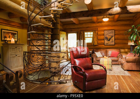 Spiral shaped wood and wrought iron staircase and red leather chair in the living room inside a 2003 built cottage - Stock Photo
