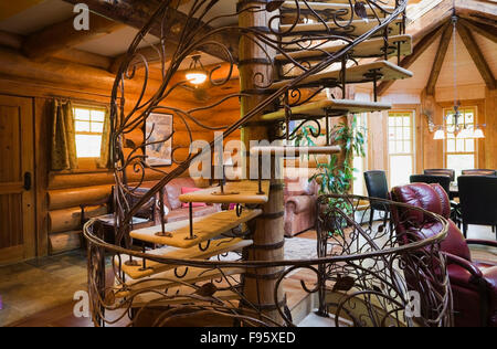 Spiral shaped wood and wrought iron staircase in the living room inside a 2003 built cottage style residential log - Stock Photo