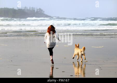A young woman and her dog (Golden Retriever) run after a ball on Chesterman Beach near Tofino, BC. - Stock Photo