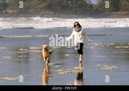 A young woman and her dog (a Golden Retriever) run with a ball on Chesterman Beach near Tofino, BC. - Stock Photo