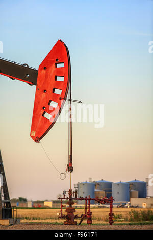 Oil pump jack in the Bakken oil field, with oil storage tanks in background, near Estevan, Saskatchewan, Canada - Stock Photo
