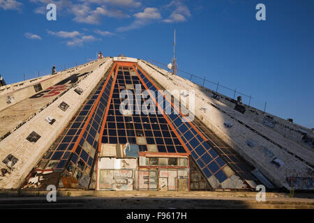 Adults and children climbing up the side of the Pyramid building that housed the former Enver Hoxha Museum, Tirana, - Stock Photo