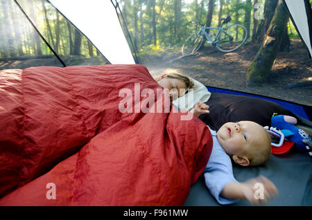 A young mother and her one year old boy in a tent on a camping trip. Mom is still trying to sleep. Rosebery Provincial - Stock Photo
