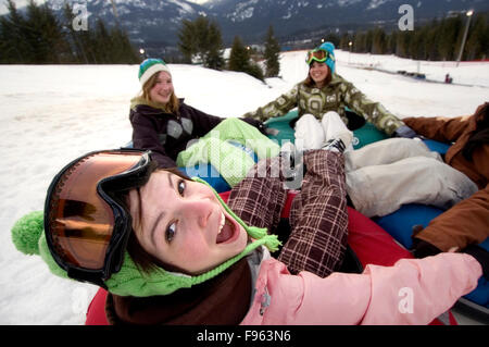 Girls laugh while playing on a giant tube at Whistler Blackcomb Tube Park, Whistler, BC Canada - Stock Photo