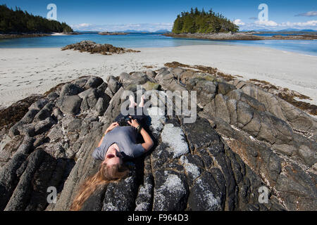 A young woman, photographer relaxes while taking pictures while visiting the McMullen group of Islets.  Great Bear - Stock Photo