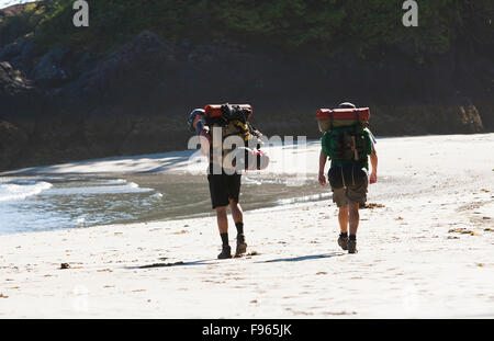 Two hikers stroll along the beach at San Jose Bay, looking for a campsite for the night.  San Jose Bay. - Stock Photo