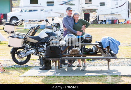 a happy mature couple packs up their campsite in preparation for a days ride on the North Island. - Stock Photo