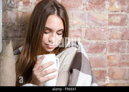 Portrait of a young beautiful woman in warm plaid holding cup with hot tea over brick wall background - Stock Photo