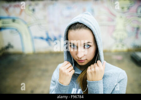 Serious teenage girl with hood on listening to music from headphones standing on background of graffiti wall