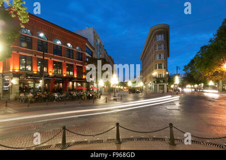 Tourist enjoy having their meals on the sidewalk cafe .Hotel Europe is a triangular heritage building or 'Flatiron' - Stock Photo