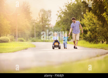 Happy young father with his two little sons have fun on road, one boy is riding on little tractor, other boy is - Stock Photo