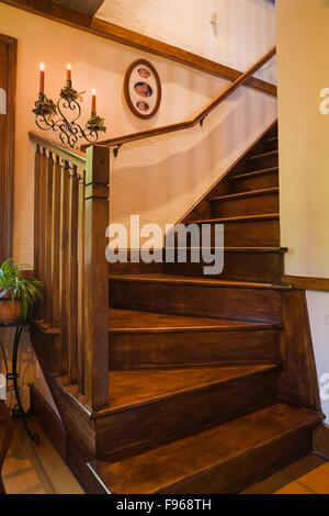 Wooden staircase leading to the upstairs floor in the living room inside a reconstructed 1840s residential log home, - Stock Photo